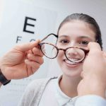Young happy woman trying her new pair of glasses after the eye exam